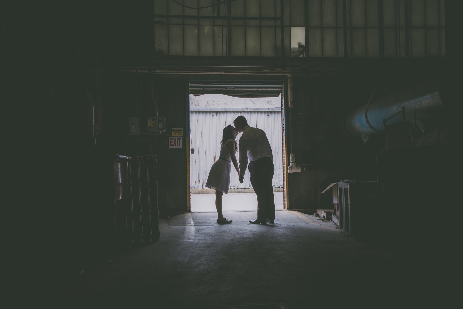 Silhouette of couple against doorway in airplane hanger in Connecticut during engagement session.