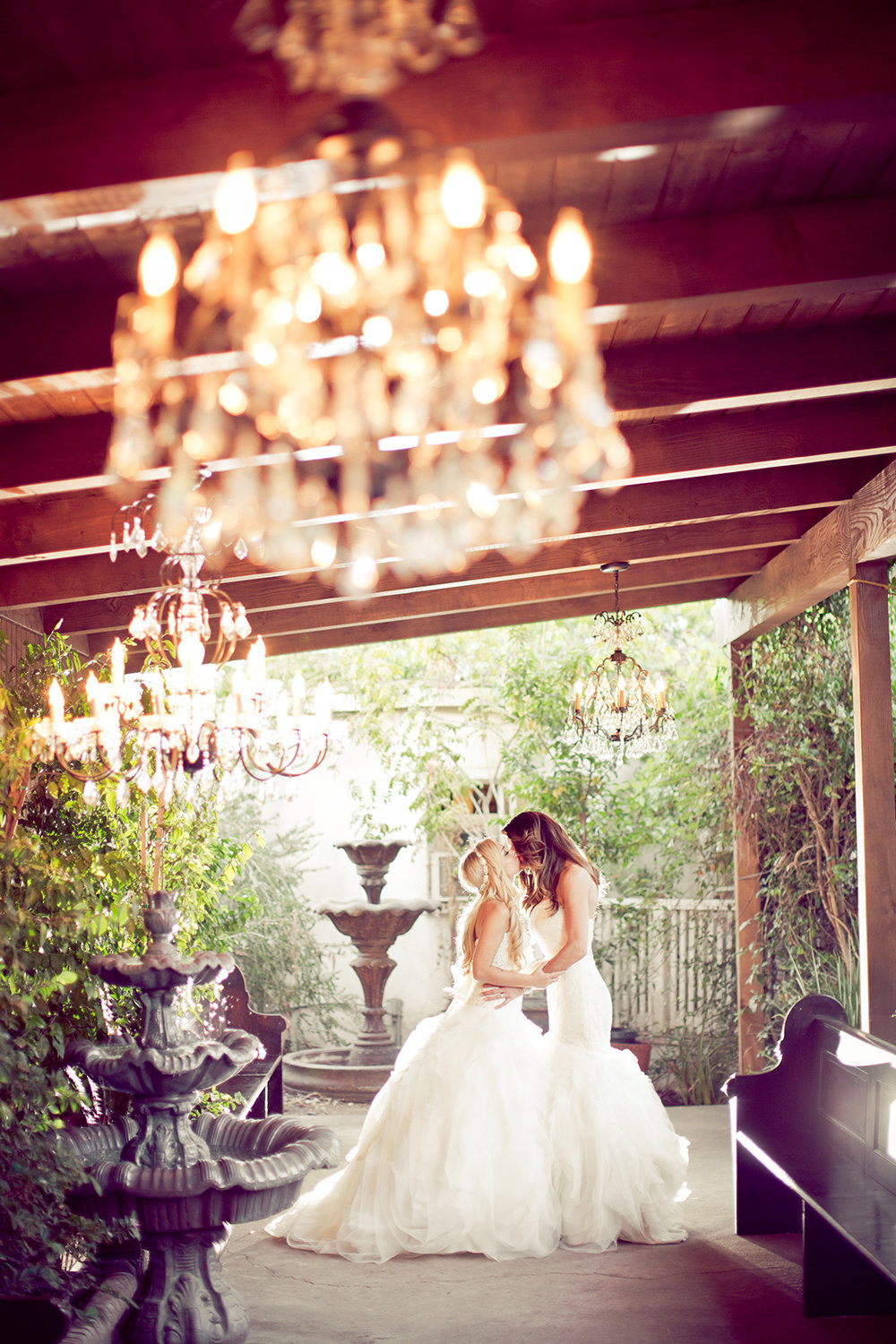 Romantic moment between two brides under chandeliers at Twin Oaks Garden Estate
