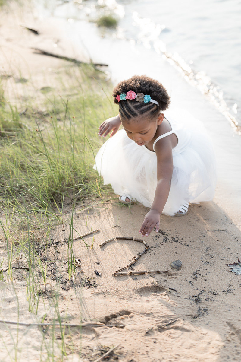toddler traces the number two in the sand at birthday photo session