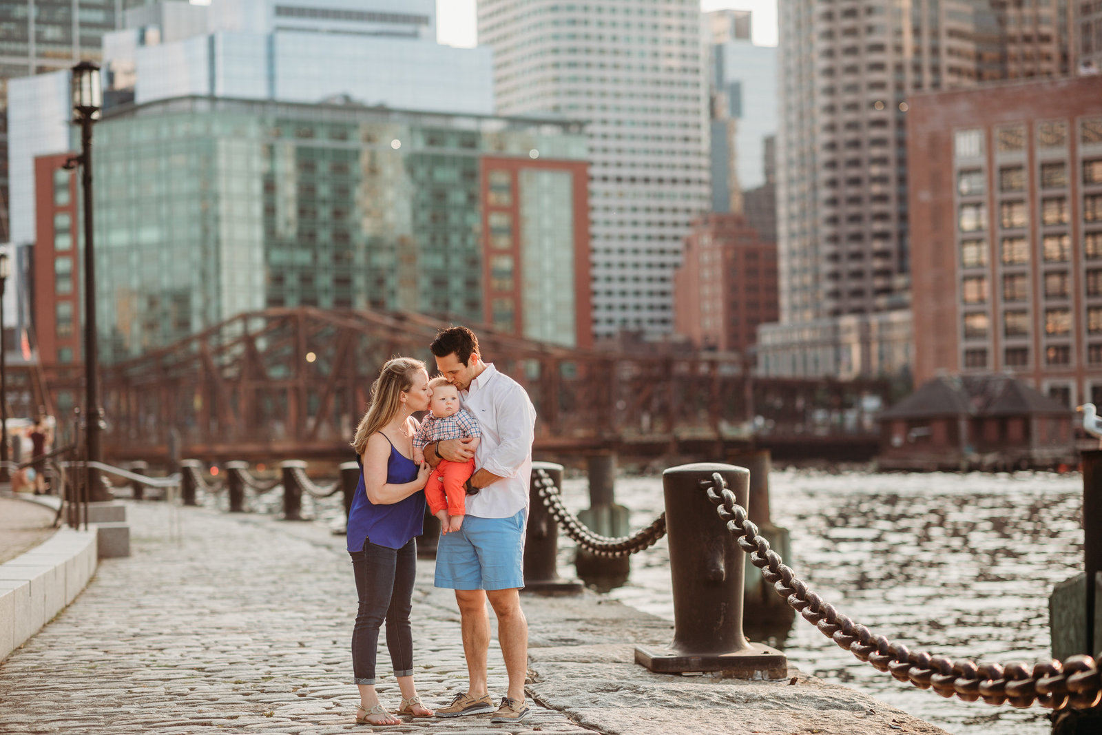 family with baby boy stands near boston skyline during family photos