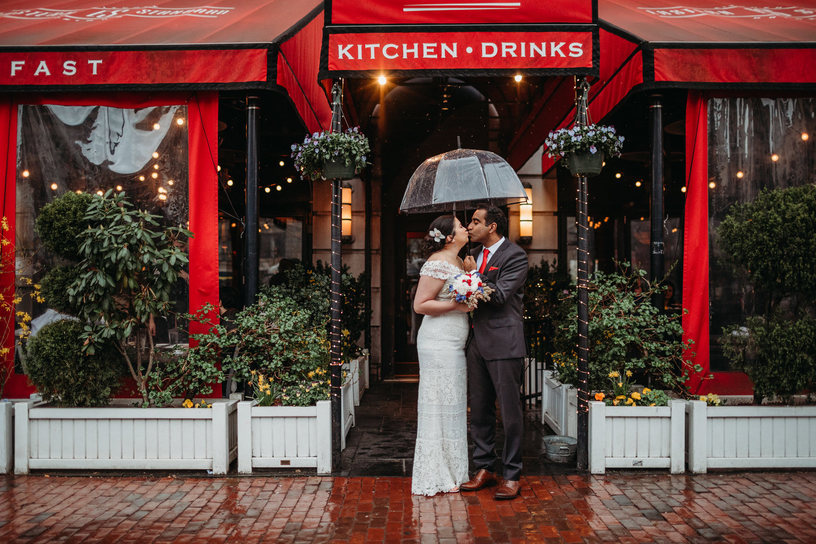 bride and groom stand under umbrella by red awning in boston