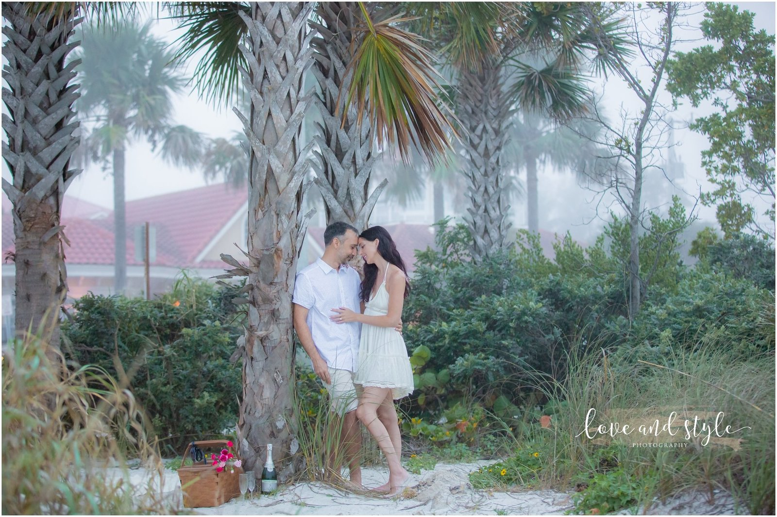 Engagement Photography with the couple by a palm tree on the bayside on Anna Maria Island, Florida