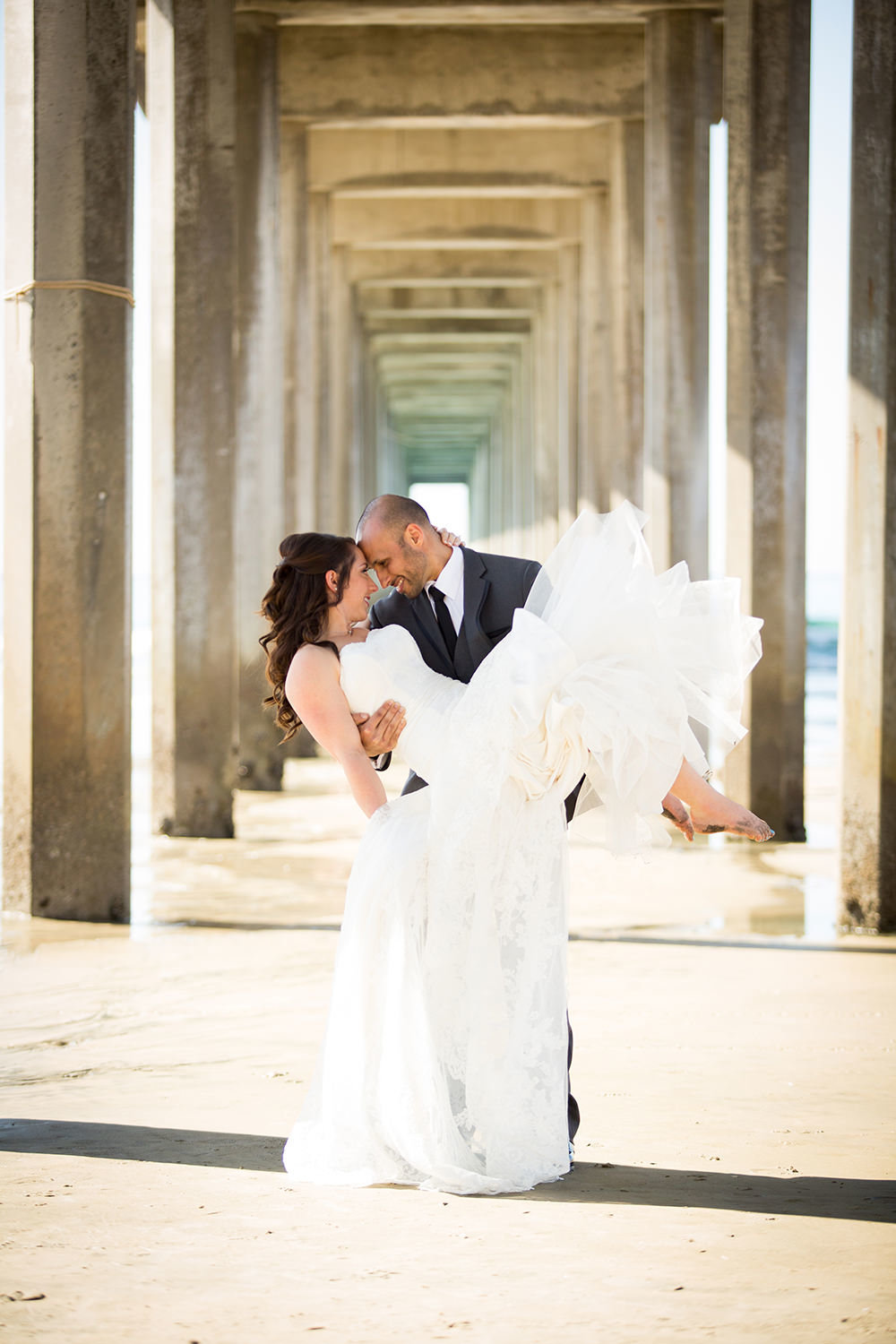 groom holding bride by scripps pier