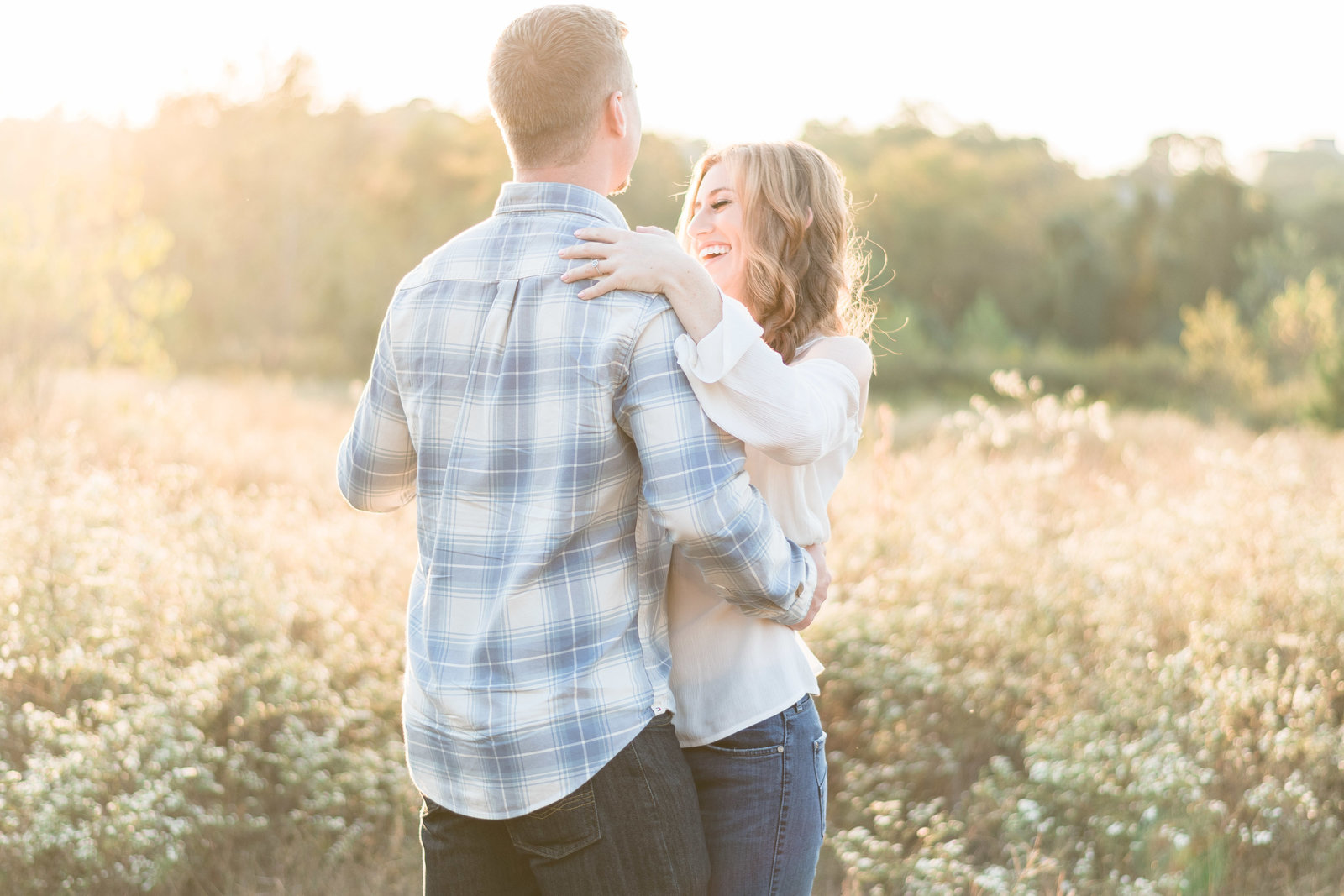 Charlotte engagement photographer shot of couple dancing in field during sunset in south park