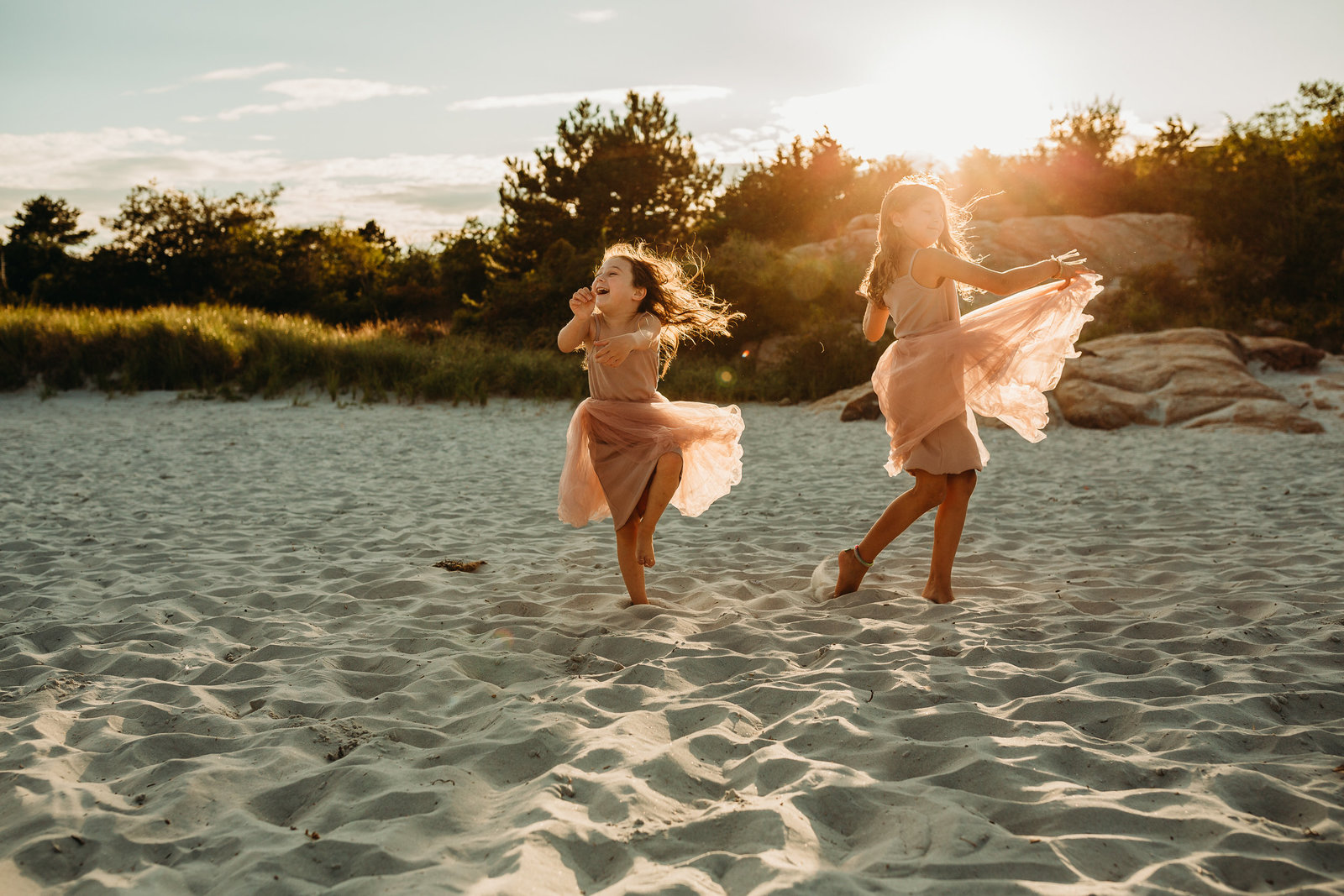 sisters dance on beach in tutus at sunset during family photo shoot in boston