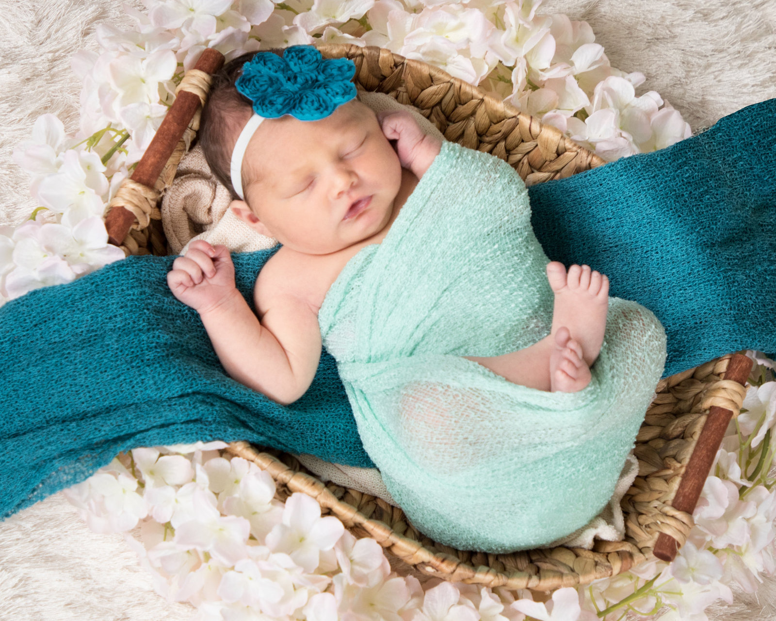 Newborn baby girl in a teal wrap on a basket