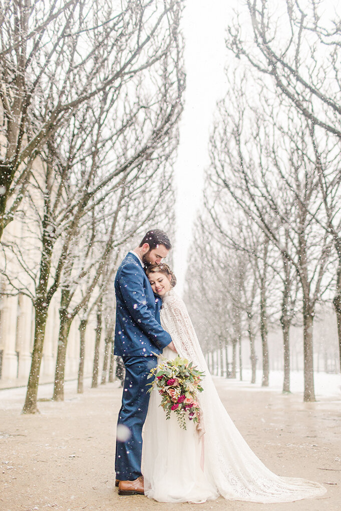 bride with her head on grooms chest and looking down at bouquet as it snows heavily in paris france
