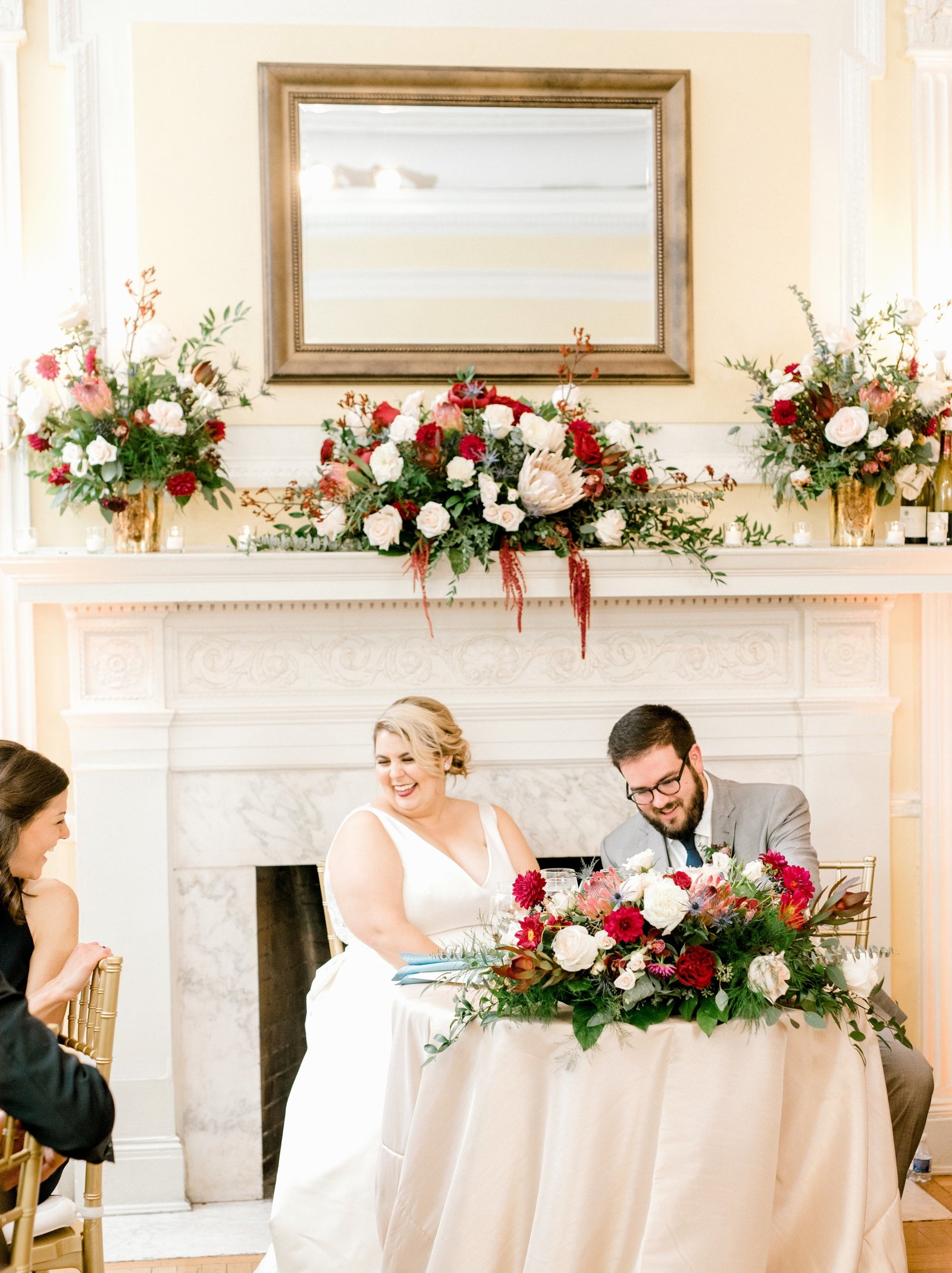 Bride and groom in front of fireplace and behind sweetheart table