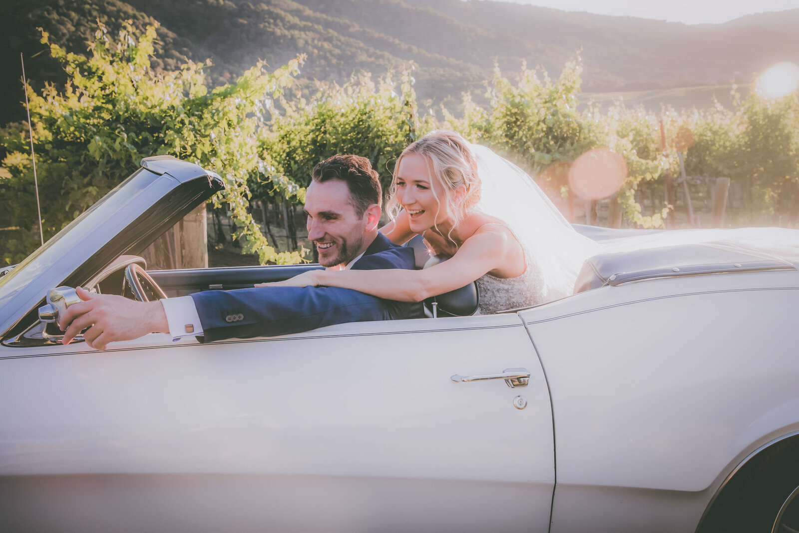 Groom and bride look into car mirror during sunset at a Carmel vineyard.