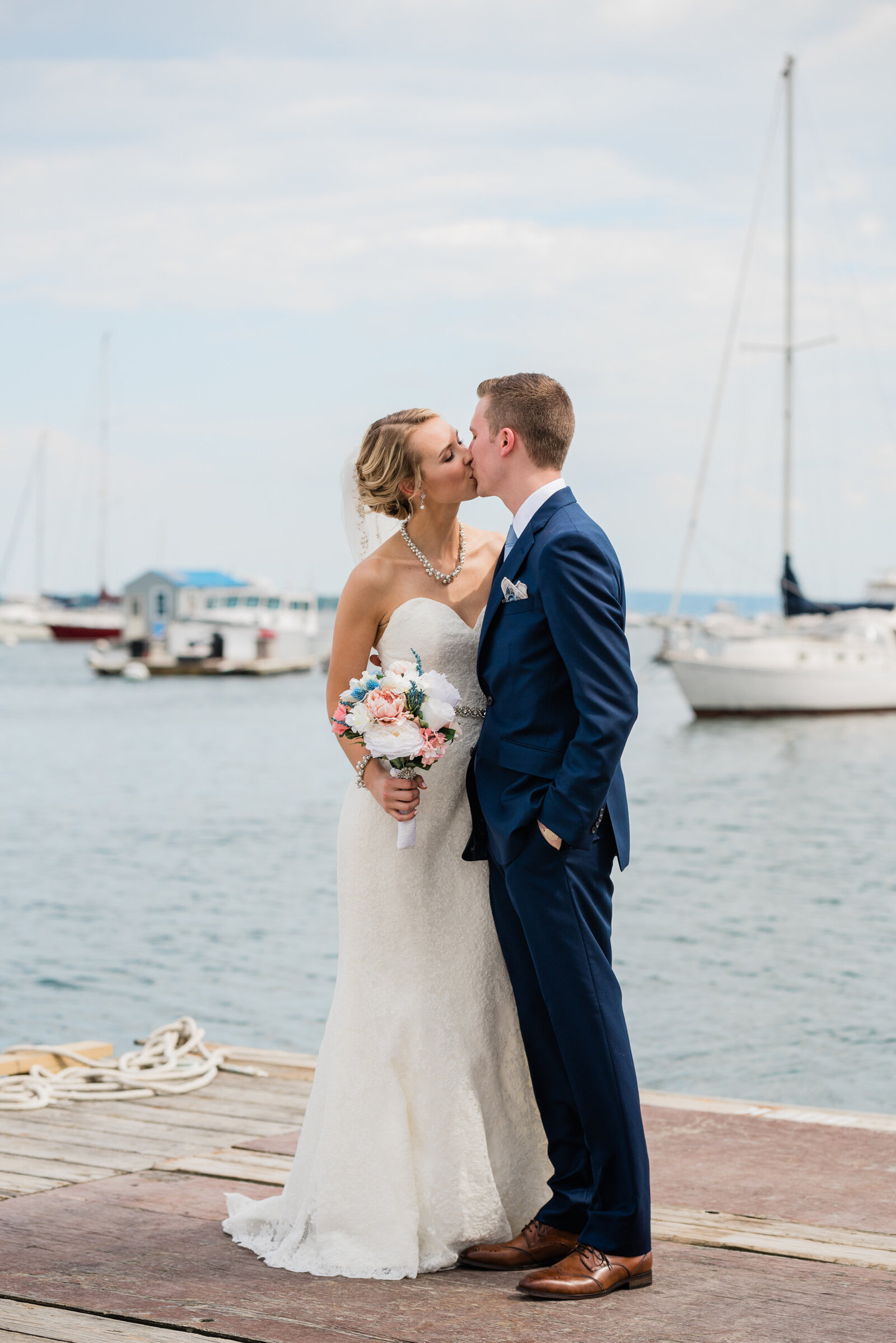 wedding couple shares a kiss during their portraits on the dock at the Duxbury Bay Maritime School