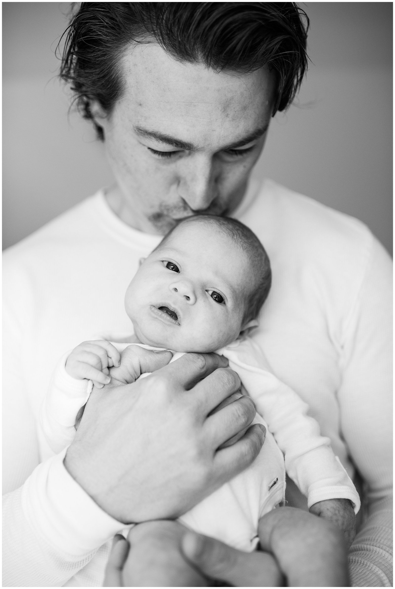 black and white close up of dad kissing newborn baby Emily Ann Photography Seattle Photographer