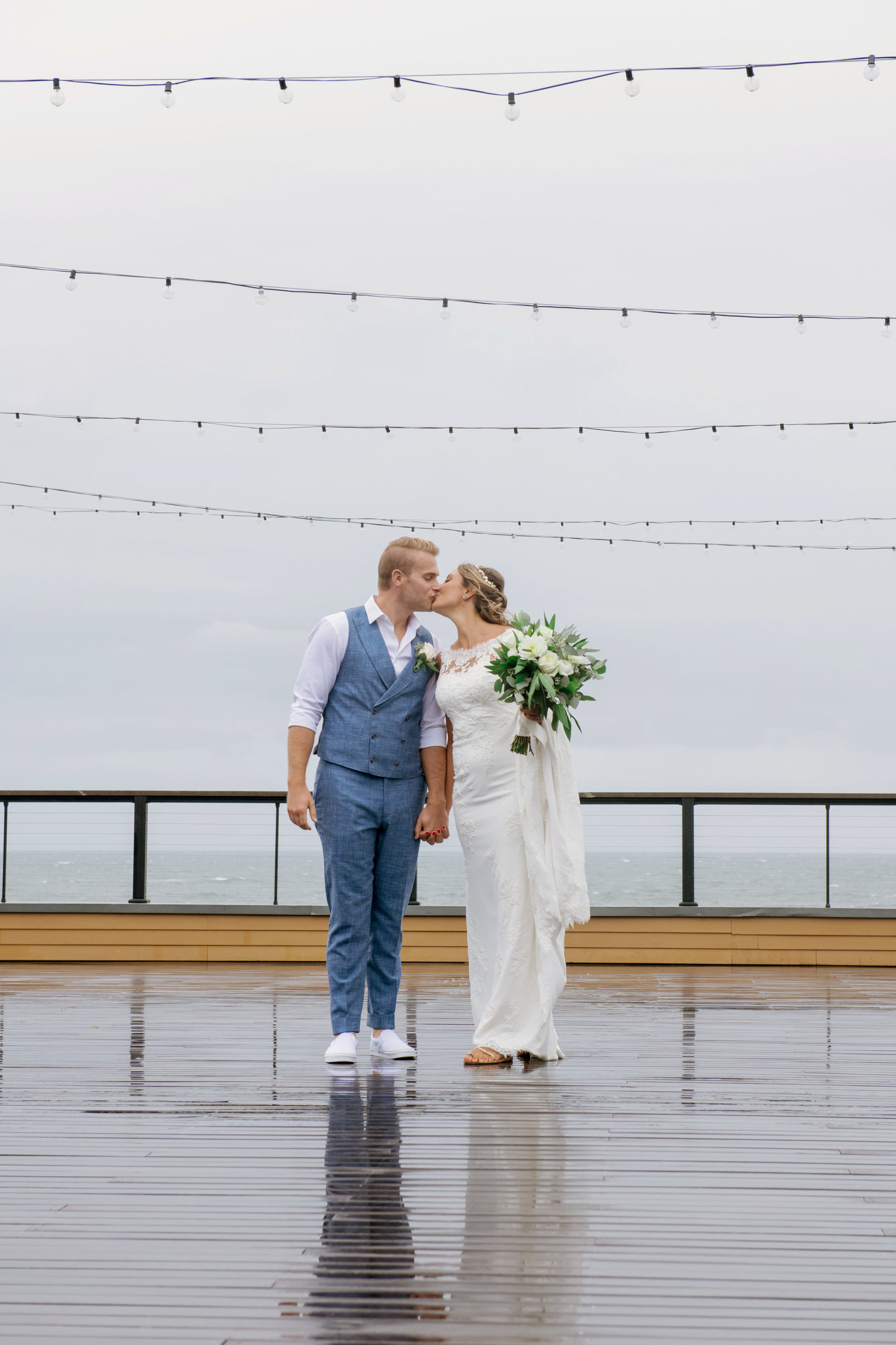 bride and groom kissing on the boardwalk deck at Gurneys Montauk Resort wedding