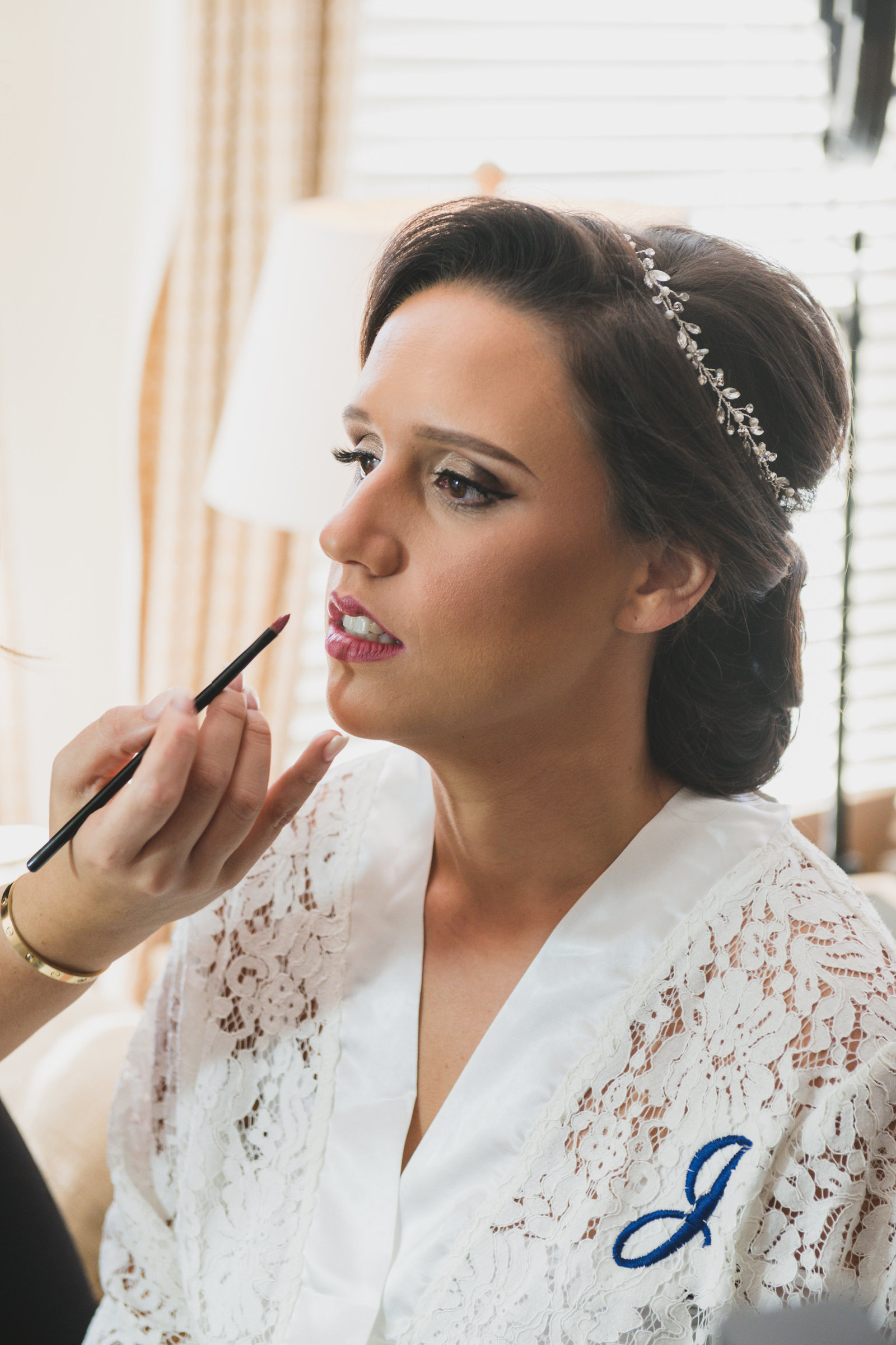 bride getting make up done from wedding at Three Village Inn