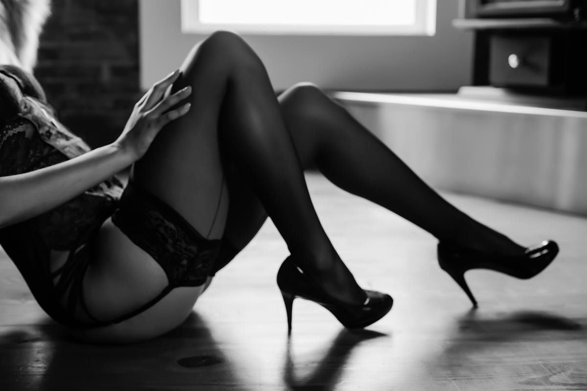 Black and white photo of a woman's legs in thigh high stockings