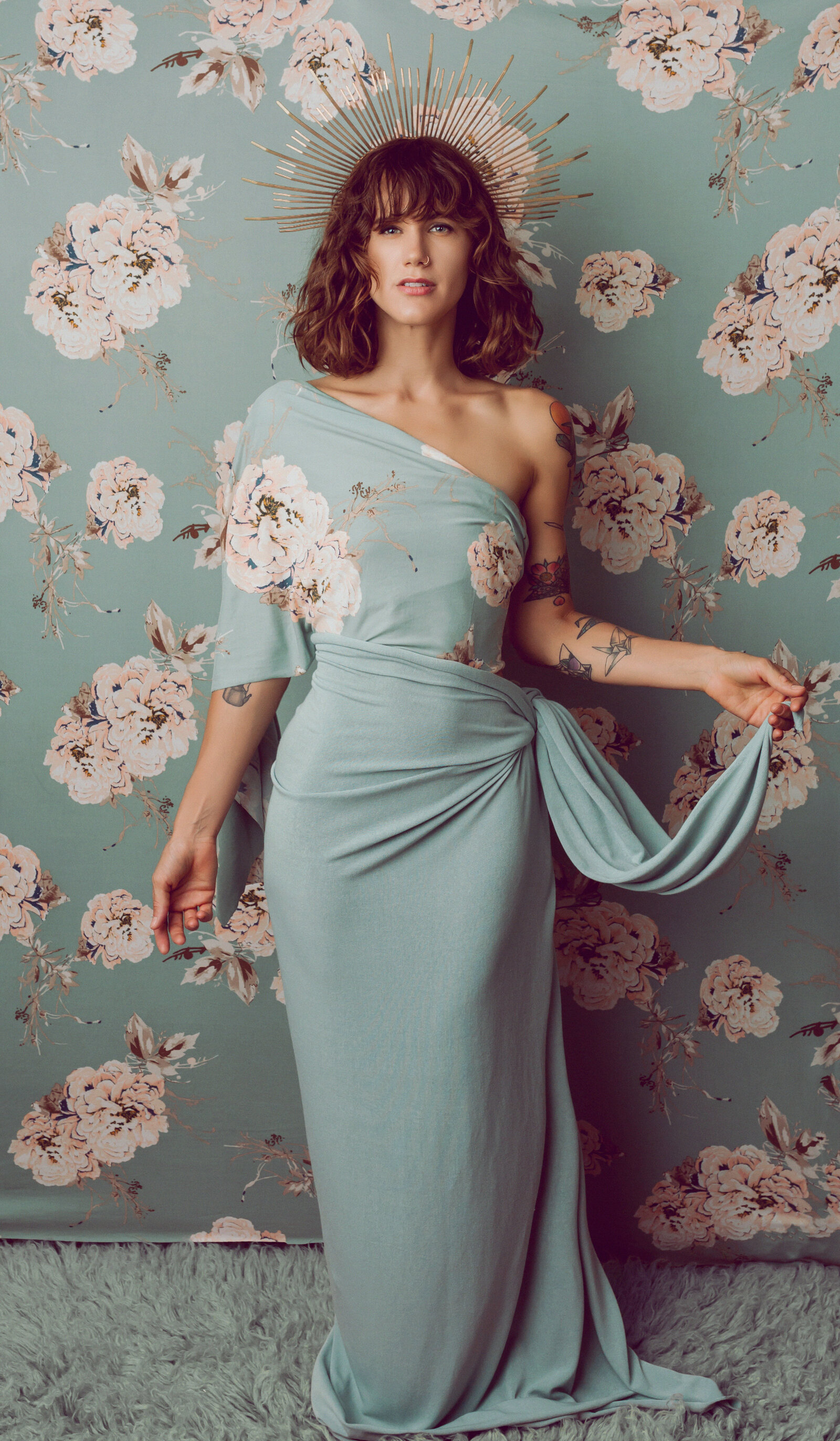 Portrait of a woman in a light blue gown in front of wallpaper that matches the gown, facing camera center.