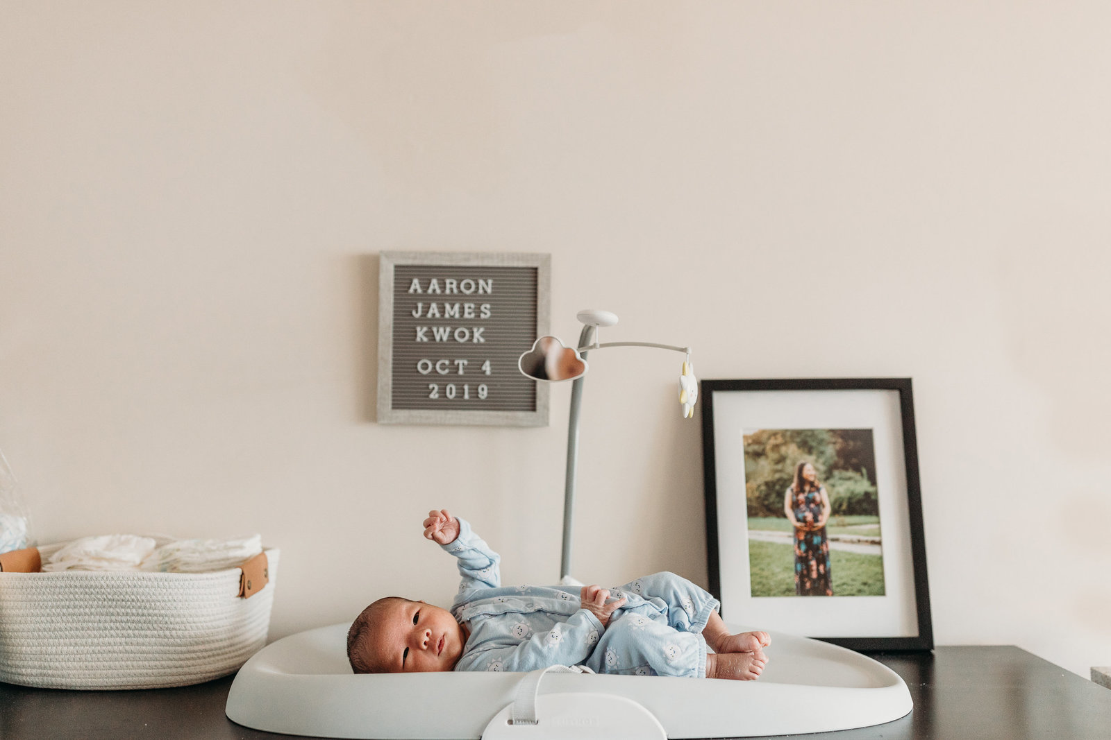 baby boy lies on changing table with one fist in the air