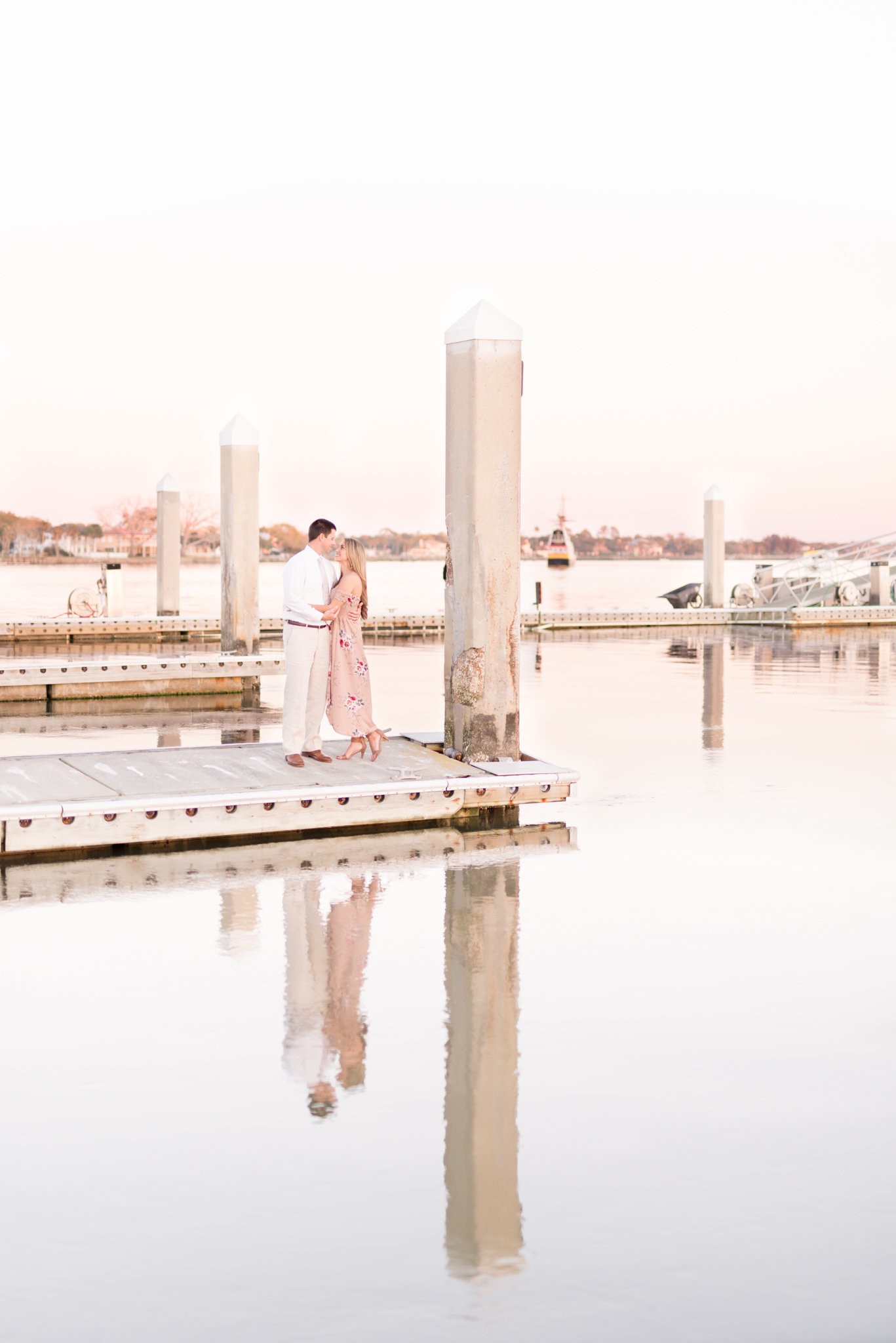Couple stands on St. Augustine dock at sunset.