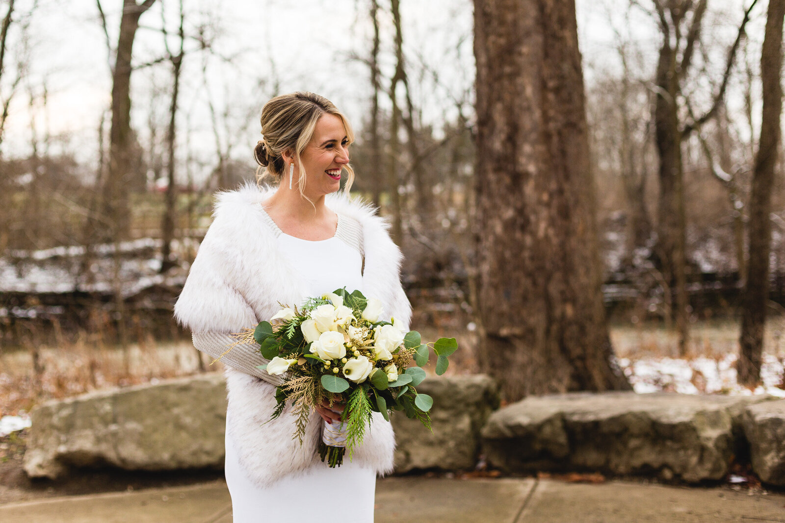 bride looking at her groom and smiling while wearing fur and holding flowers at winter wedding ohio