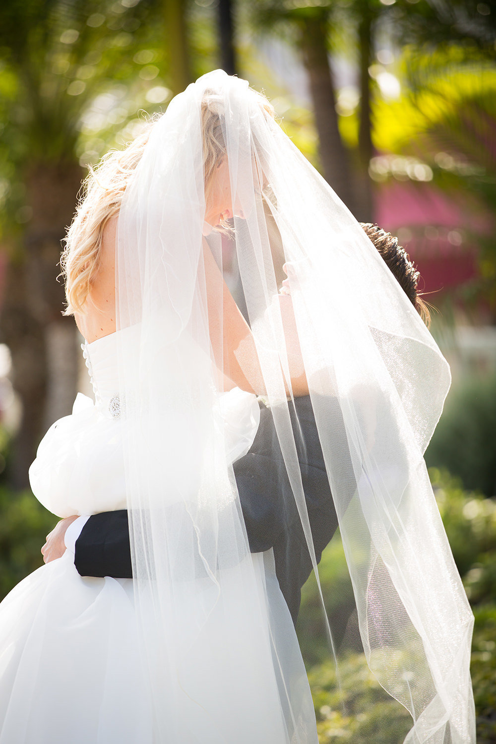 Great moment of groom lifting the bride with flowing veil