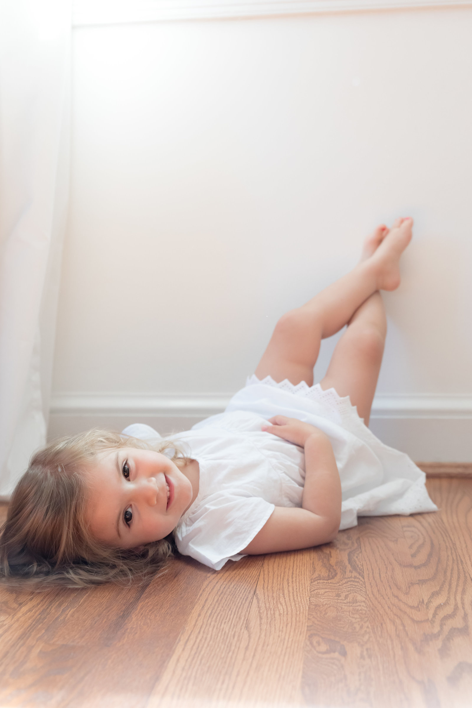 big sister lays on her back in white dress during lifestyle newborn session