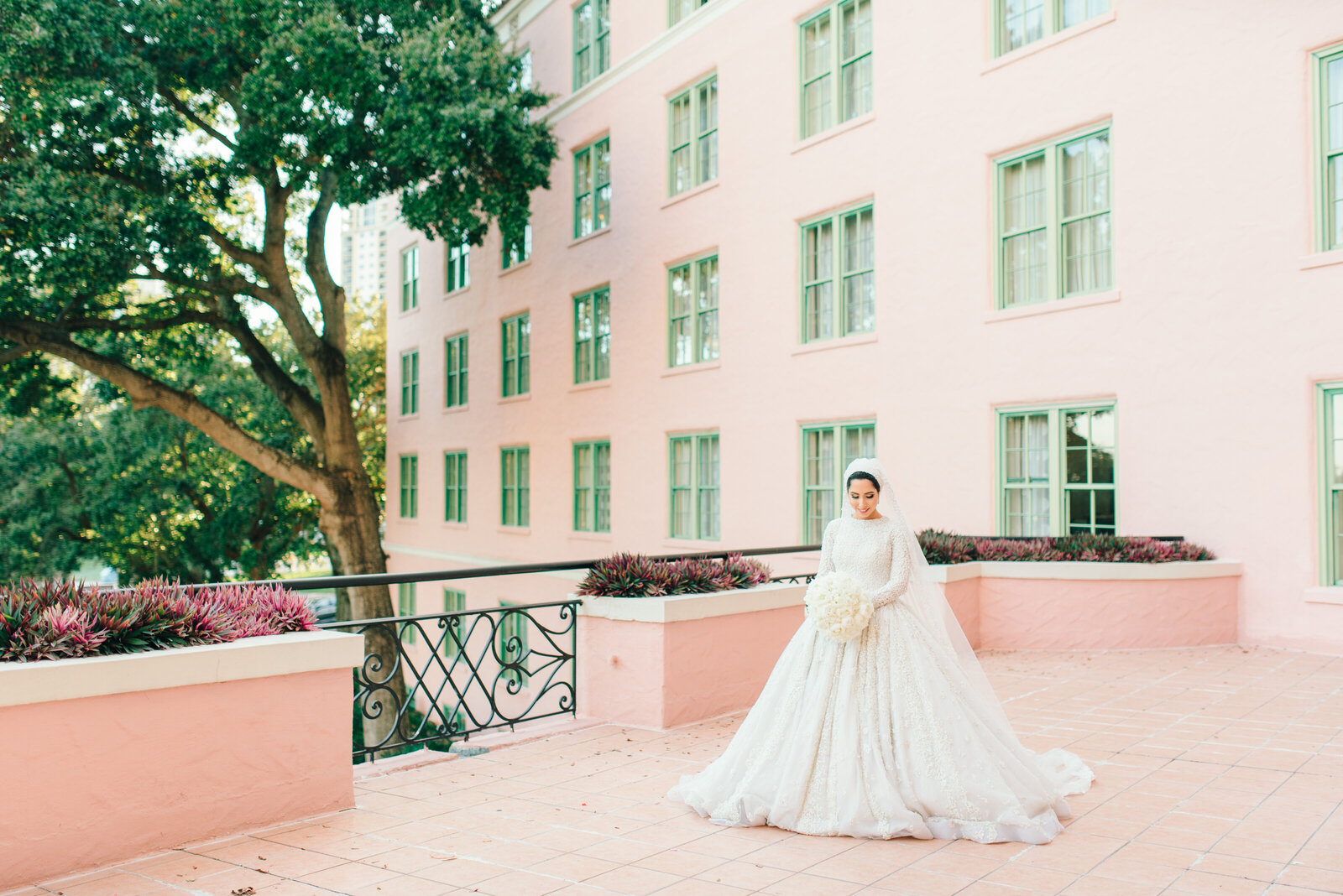 Bride wearing a luxury gown by bougainvillea at John and Mable Ringling Museum of Art in Sarasota