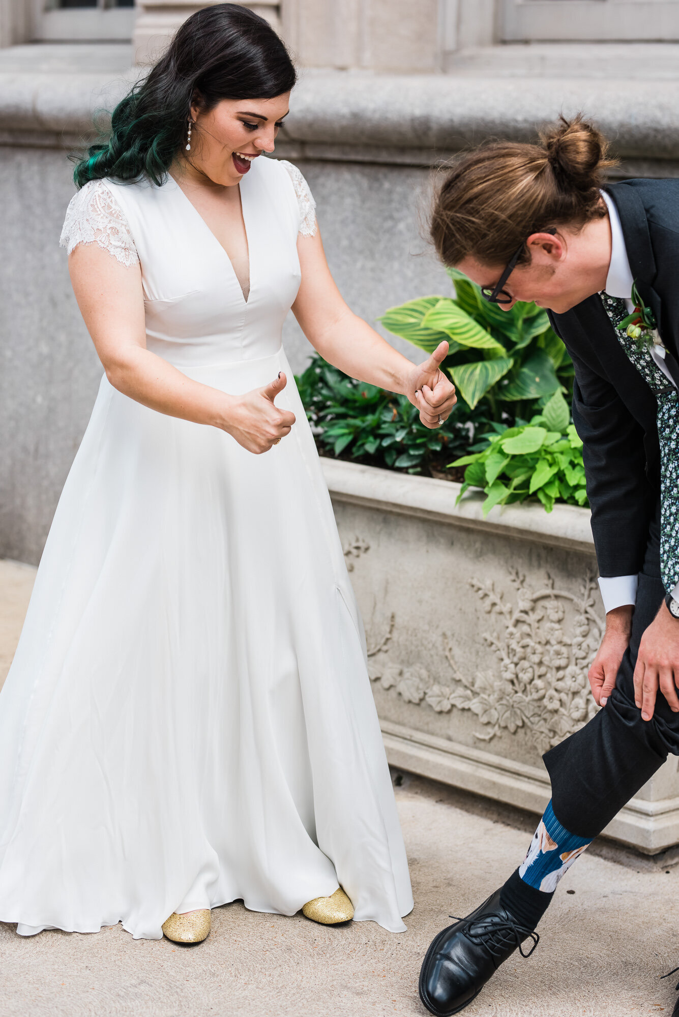 Bride gives groom thumbs up as he shows her his socks before their St. Louis wedding