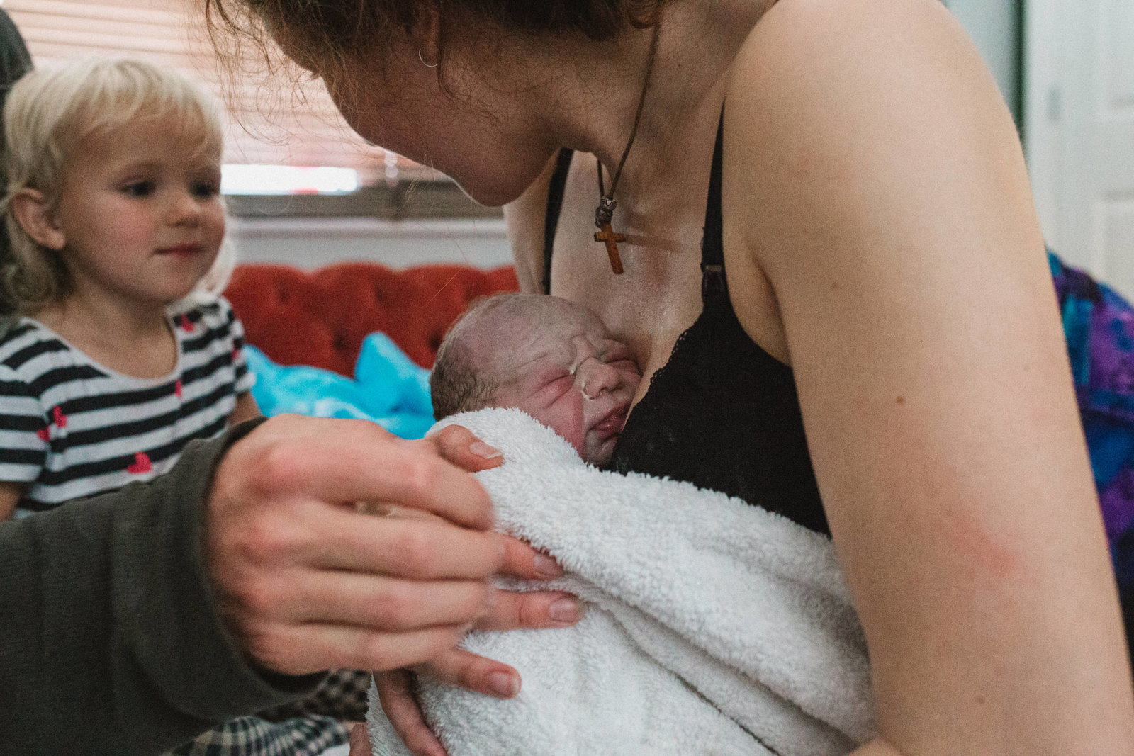 Documentary photograph of Ipswich mum holding newborn baby seconds after home birth