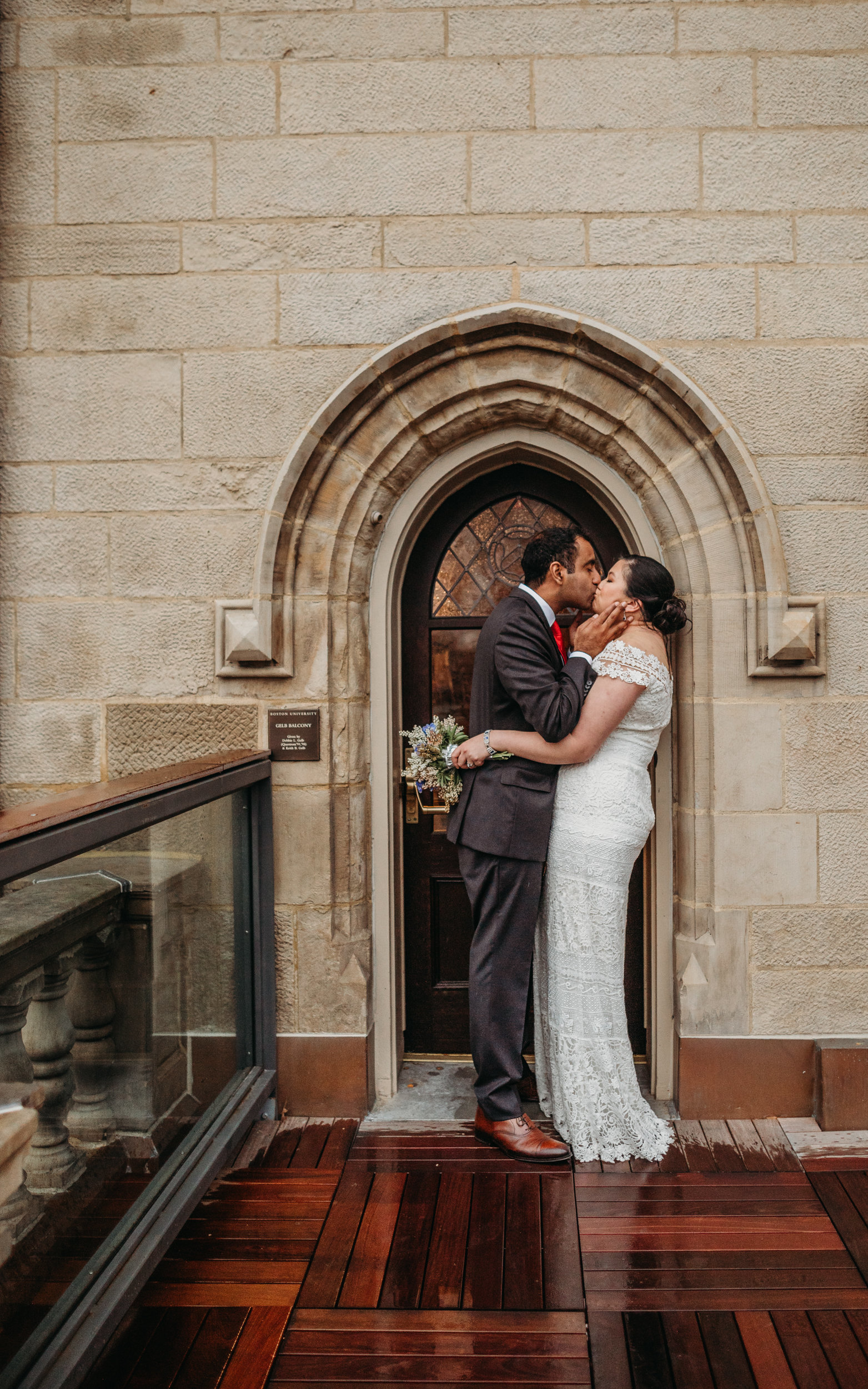 bride and groom kiss in doorway of old stone building in boston ma