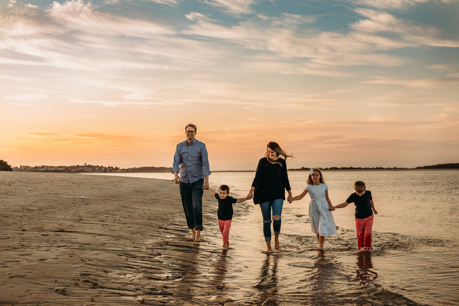 family of five holds hands and walks across beach in boston during sunset