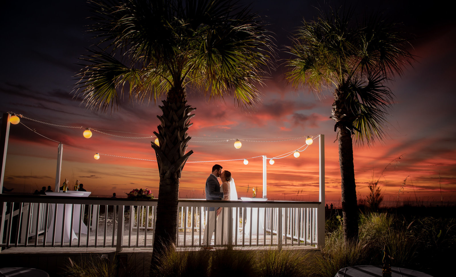 Backlight shot of bride and groom at sunset at The Sandbar in Bradenton, Florida