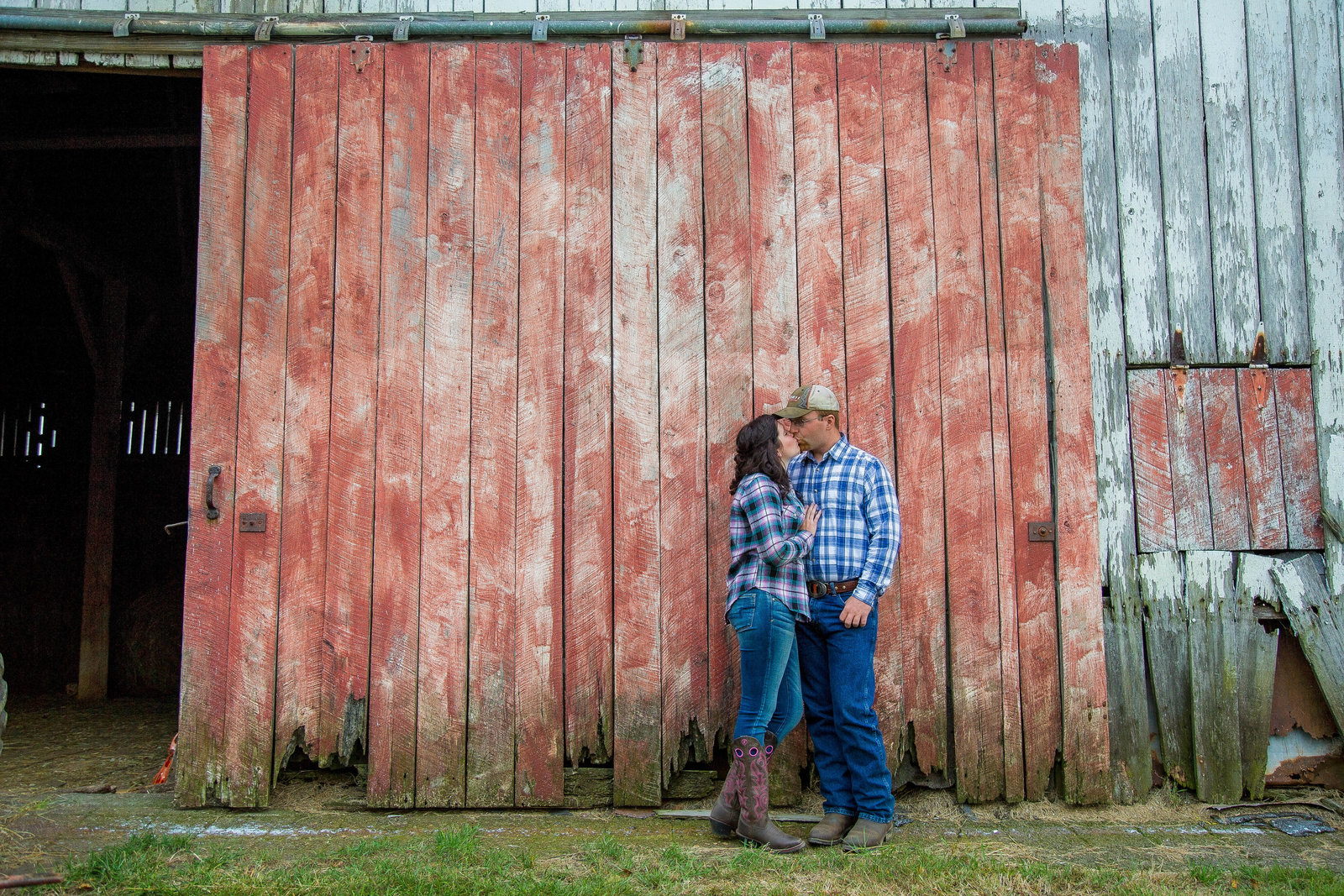 couple stand in front of barn on their farm in Irwin
