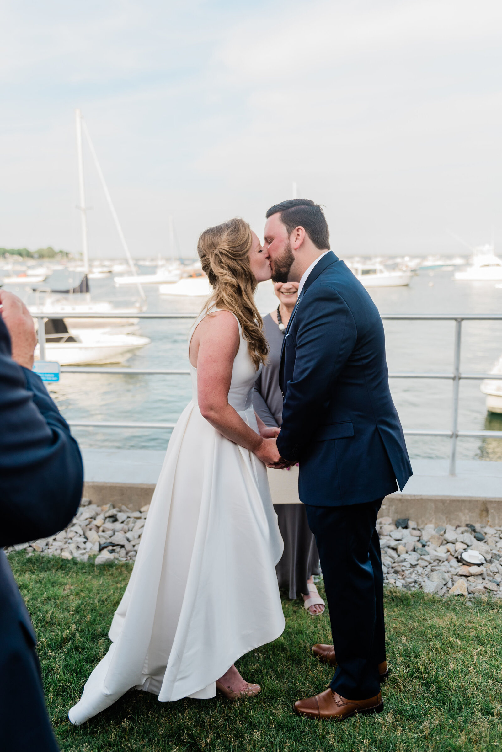 couple shares their first kiss after their waterfront wedding ceremony at Duxbury Bay Maritime School