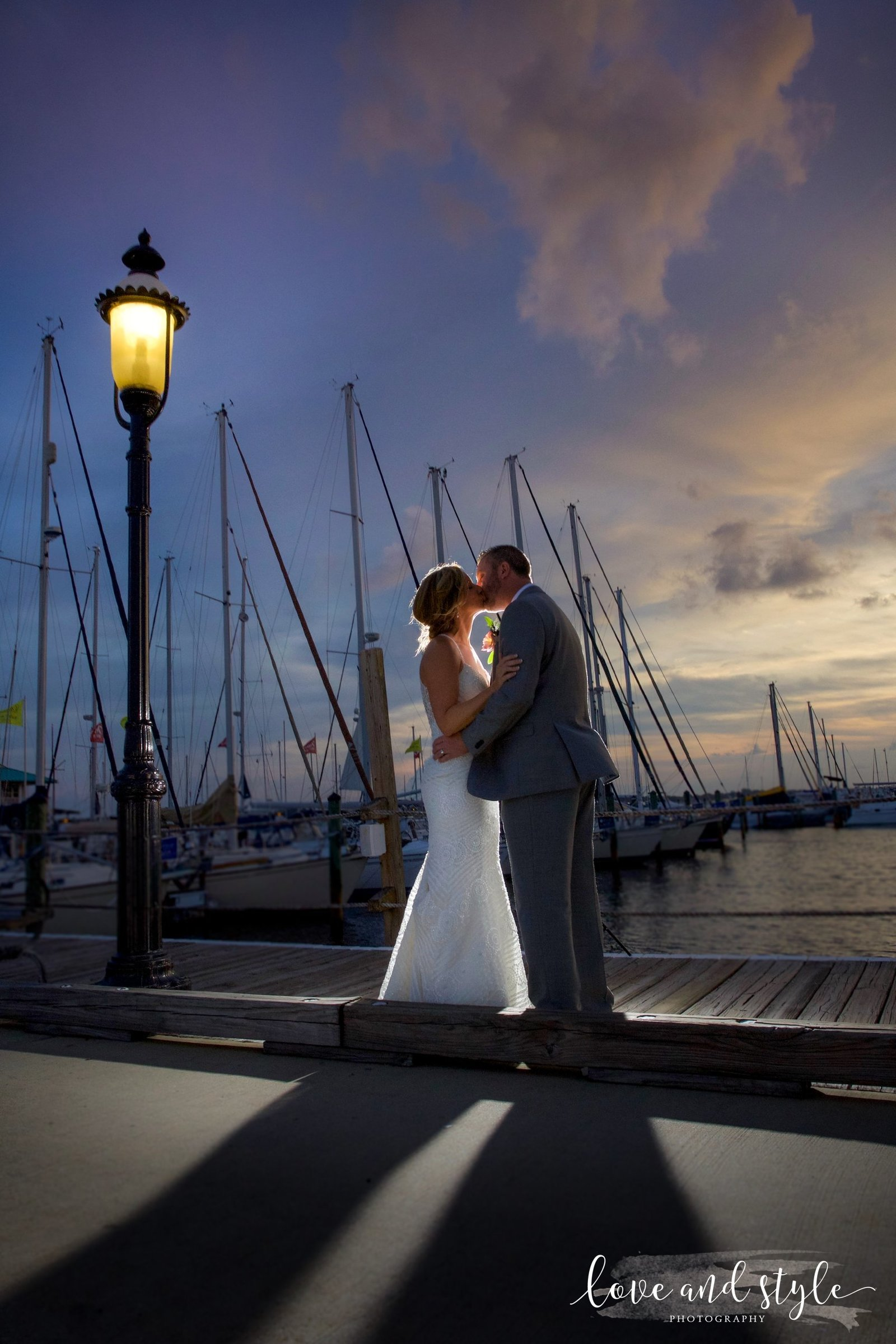 Riverhouse Reef and Grill Wedding Photography, bride and groom kissing on the dock with boats and sunset in the background