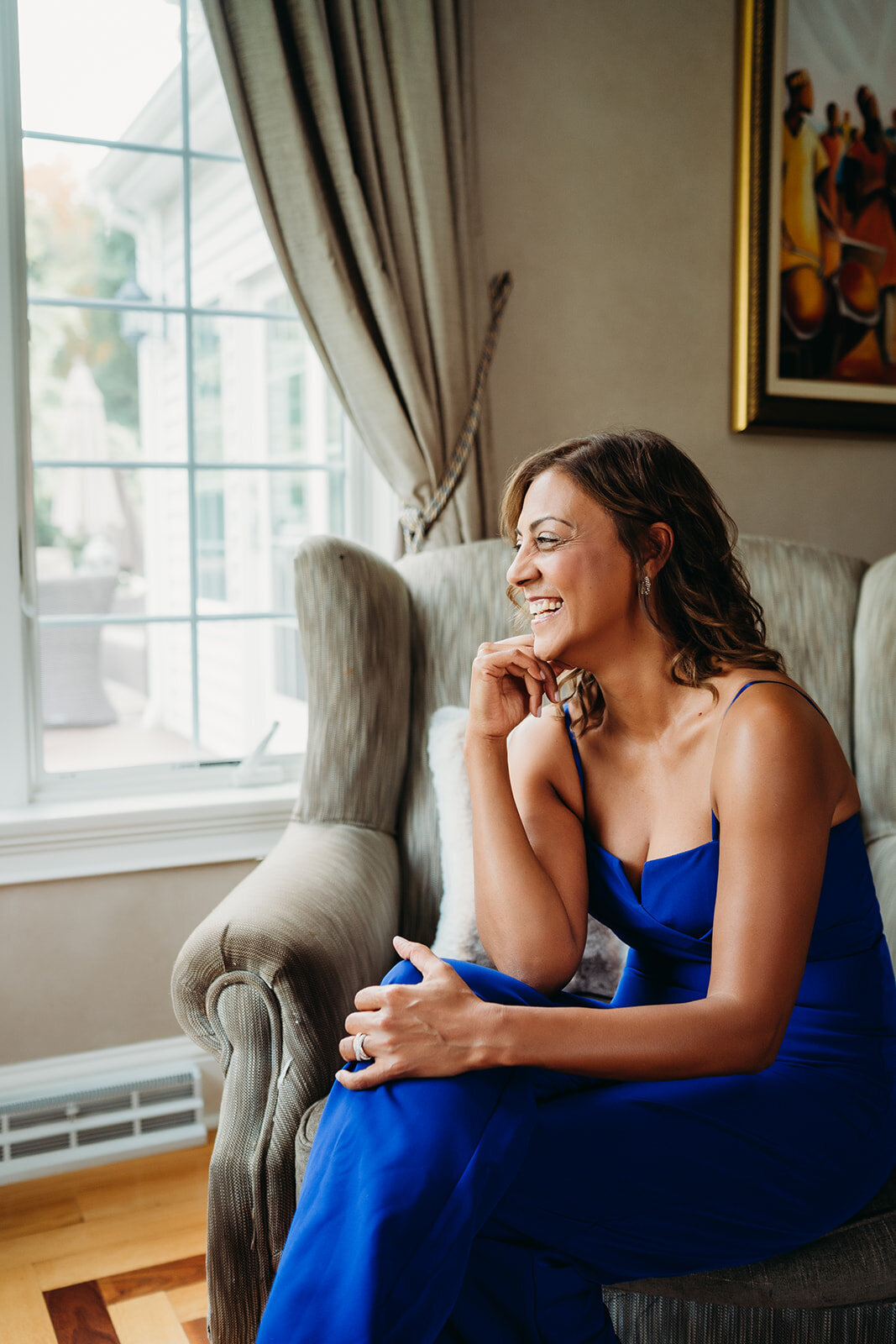 woman in blue jumpsuit looks out window and smiles
