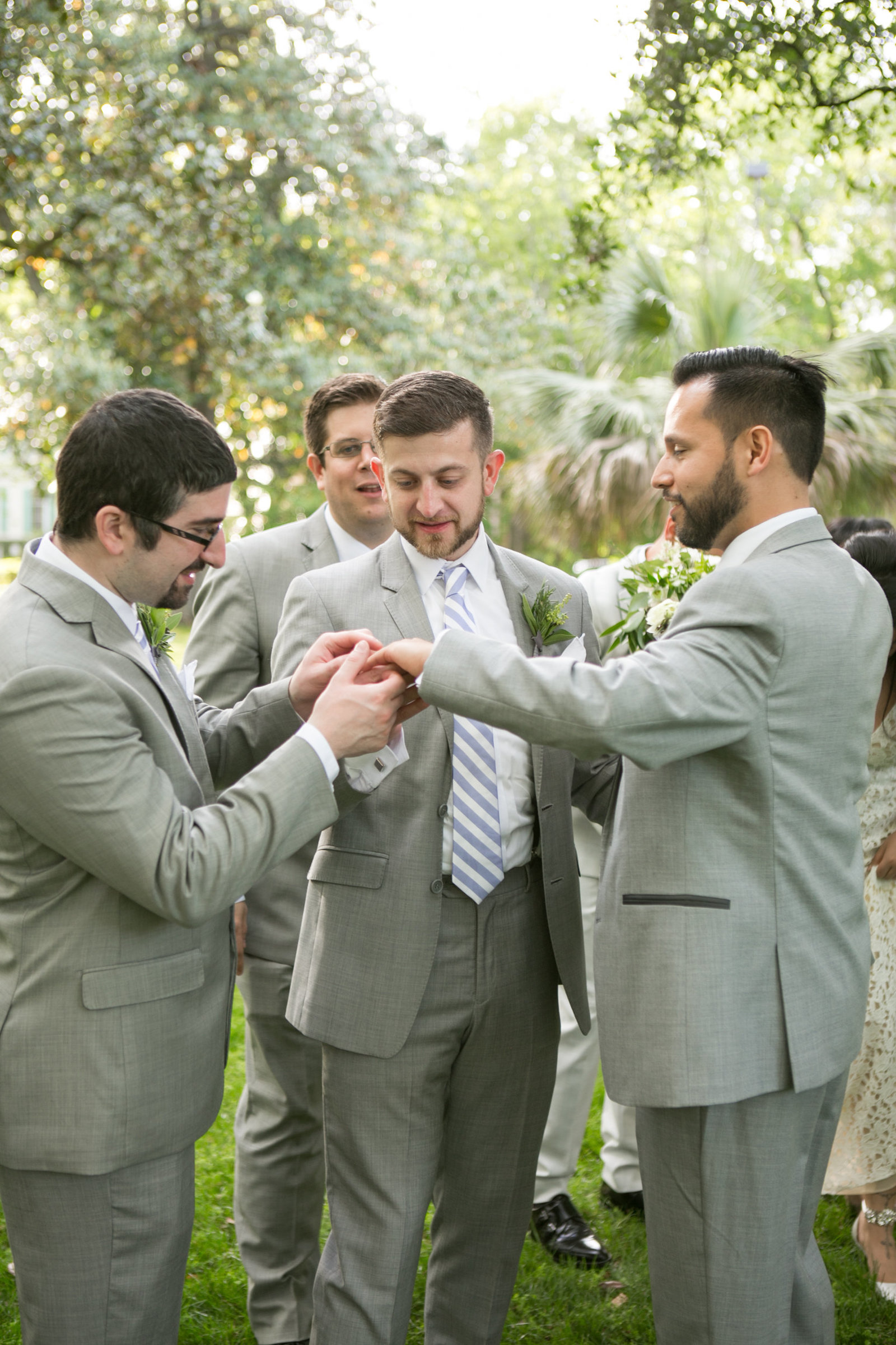 groomsmen holding hand of groom and looking at his new wedding band