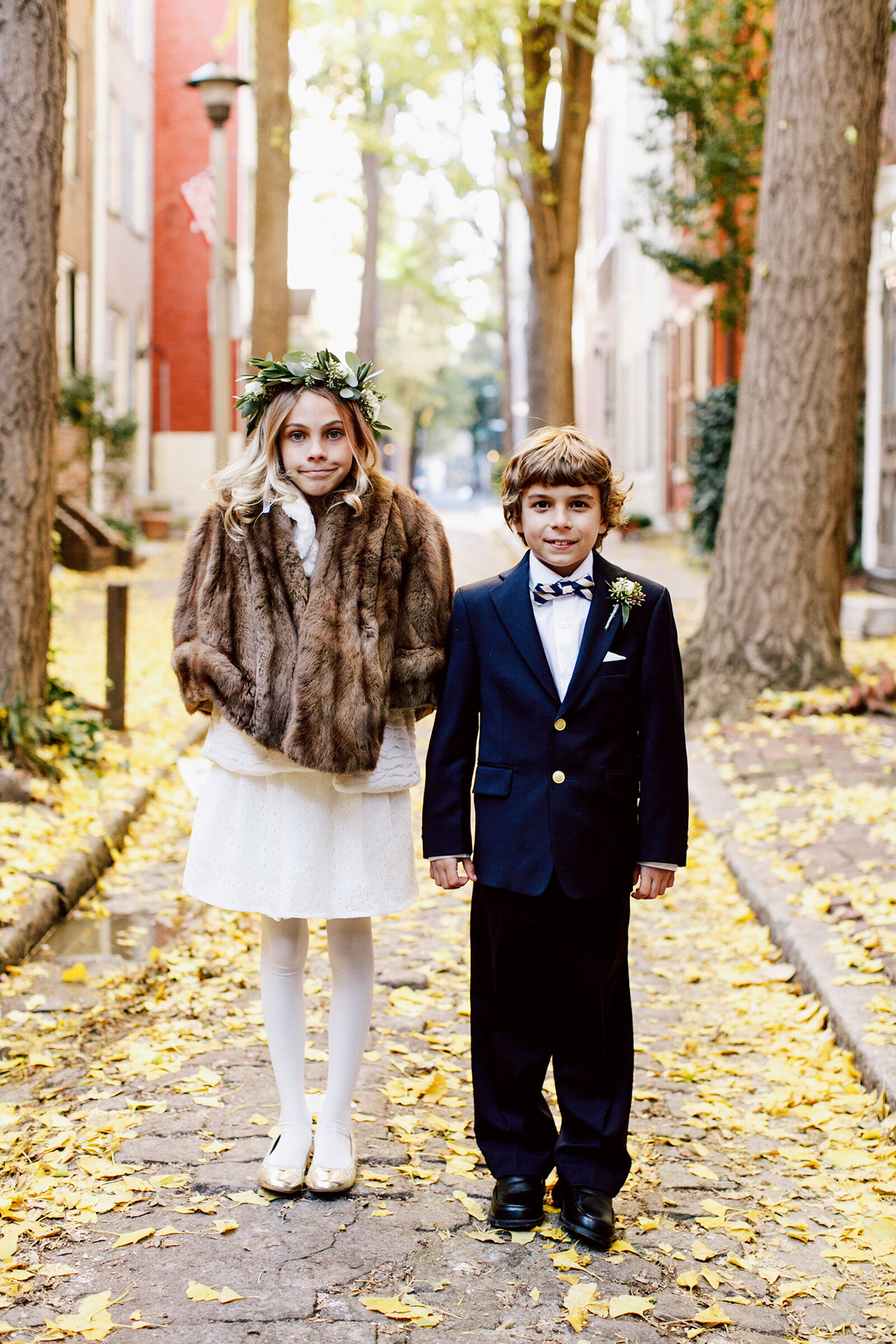 flower girl and ring bearer in city fall leaves
