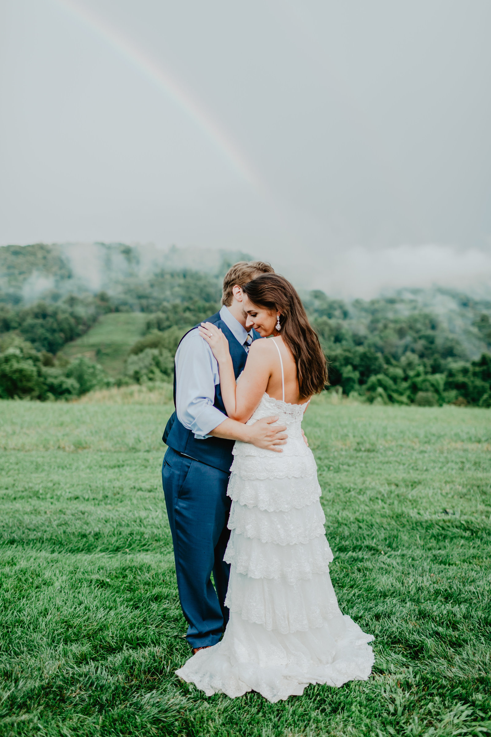 After the rain comes the most perfect fog and rainbow with Groom leaning down to whisper in his Brides ear at Chateau Silah