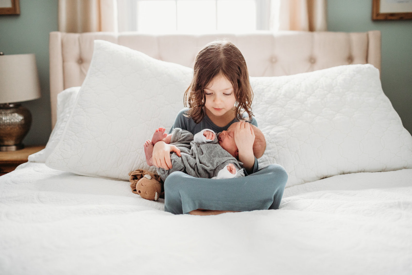 big sister holds newborn baby brother on white master bed during boston newborn photos