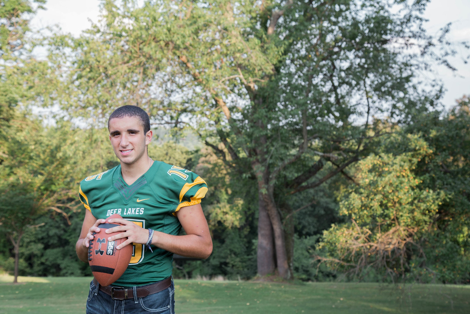 senior boy wearing football jersey stands in field at hartwood acres