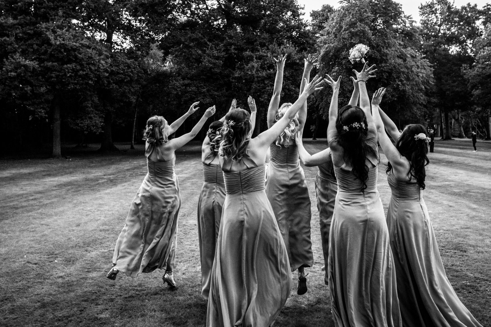 Bridesmaids stand with their backs toward the camera. They're standing in a Norfolk field and are all jumping to grab the bouquet which has been thrown by the bride.