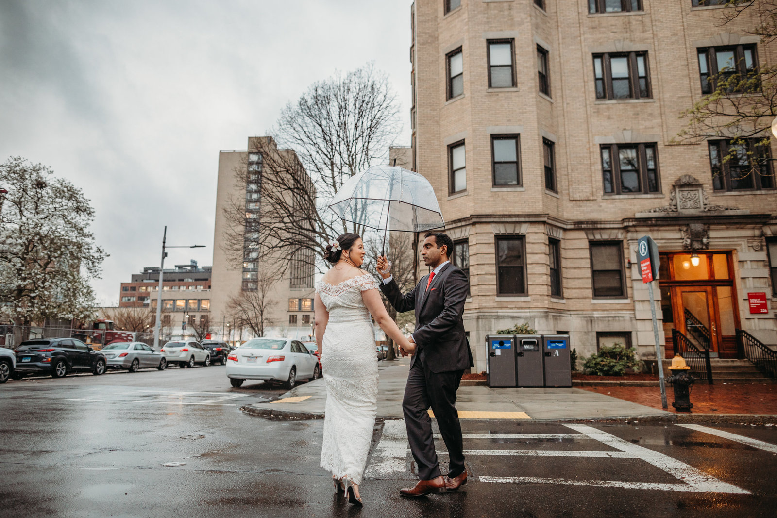 grooms holds umbrella for bride on rainy wedding day in boston ma