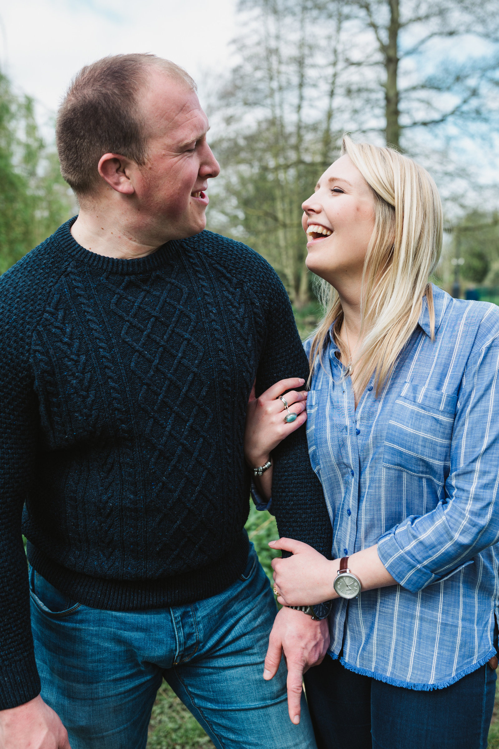 Laughing engaged couple linking arms in Ipswich for a natural photo