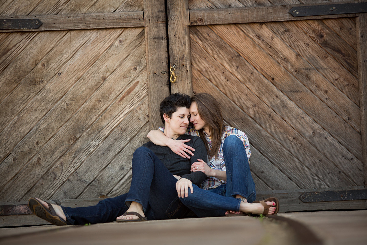Lesbian engagement session in front of barn door