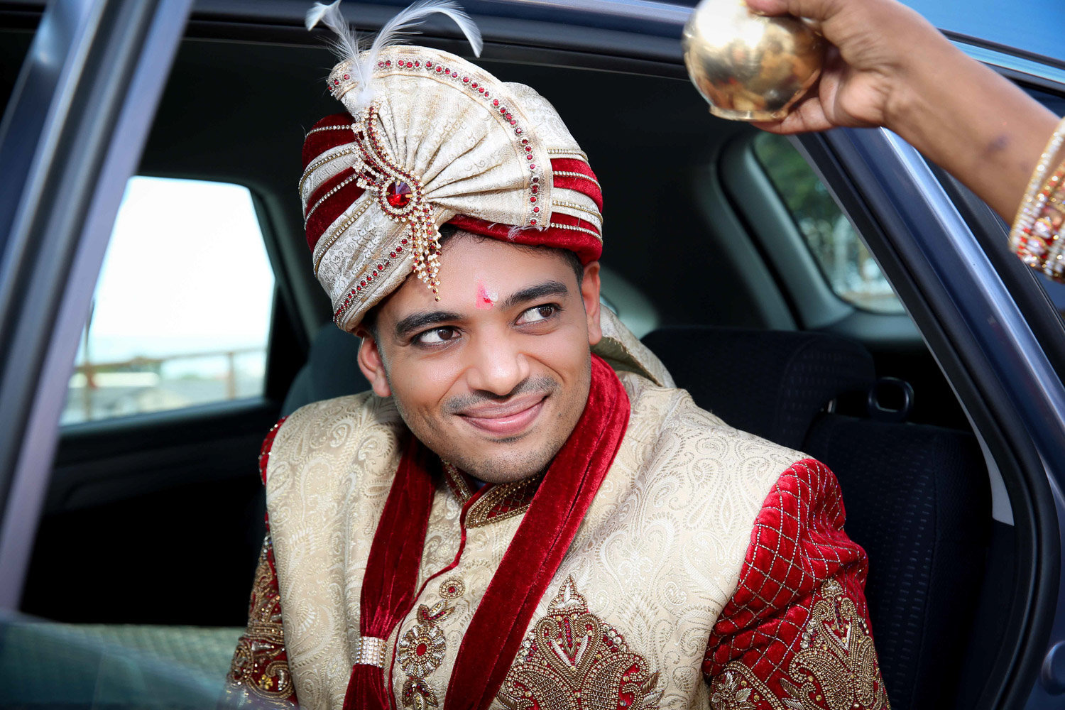 Indian groom receives blessing while coming out of car. Photo by Ross Photography, Trinidad, W.I..