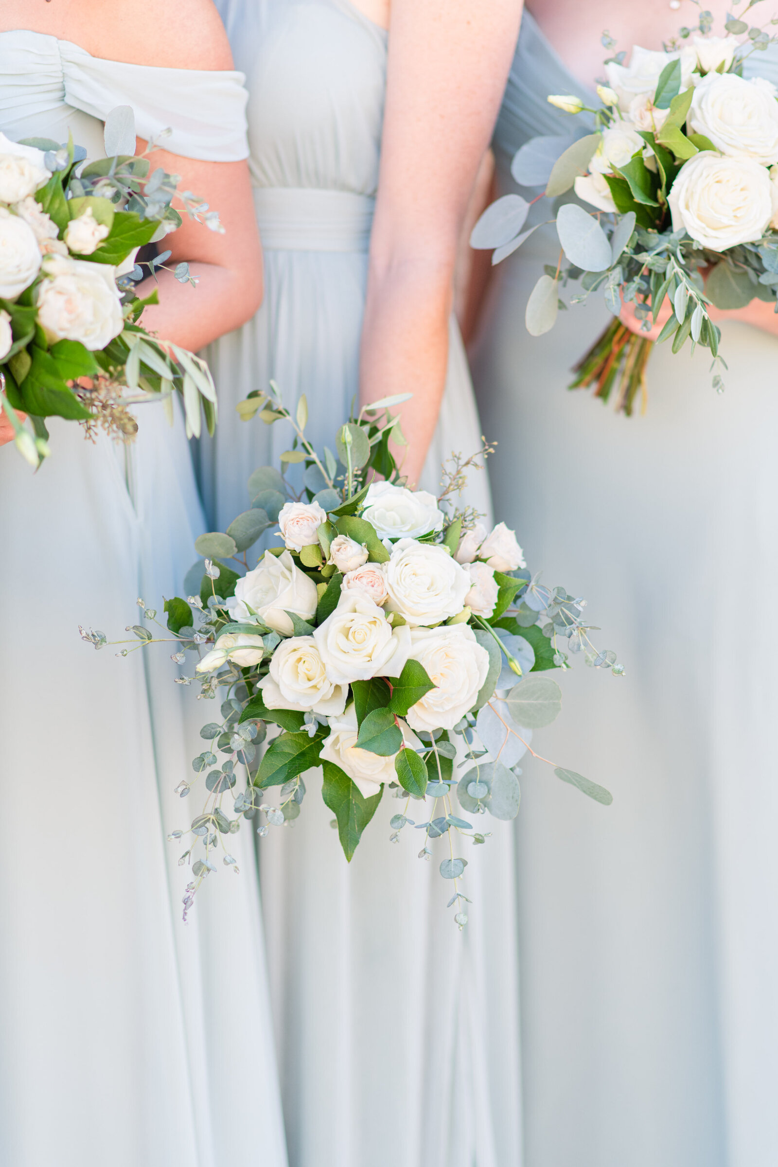 bridesmaids in light sage green dresses with white bouquets