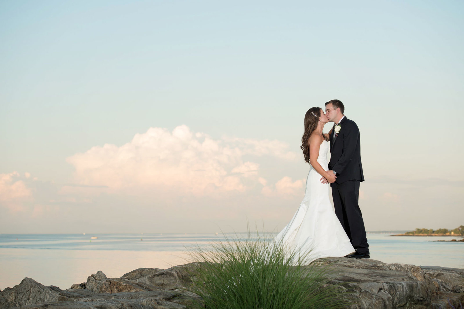 bride and groom kissing by the water at Glen Island Harbor Club