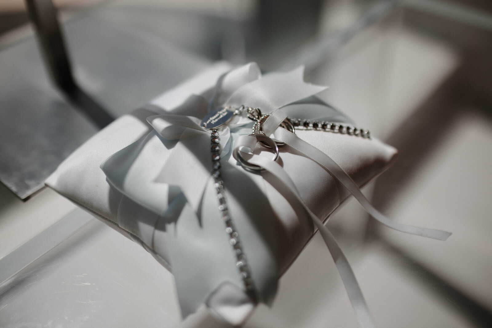 close-up-of-wedding-rings-on-white-pillow