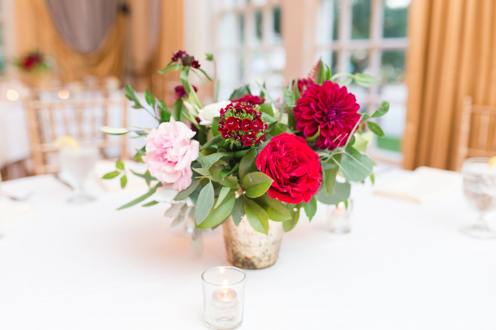 blush red and burgundy centerpiece from everly alaine florals at a luxury hotel wedding reception