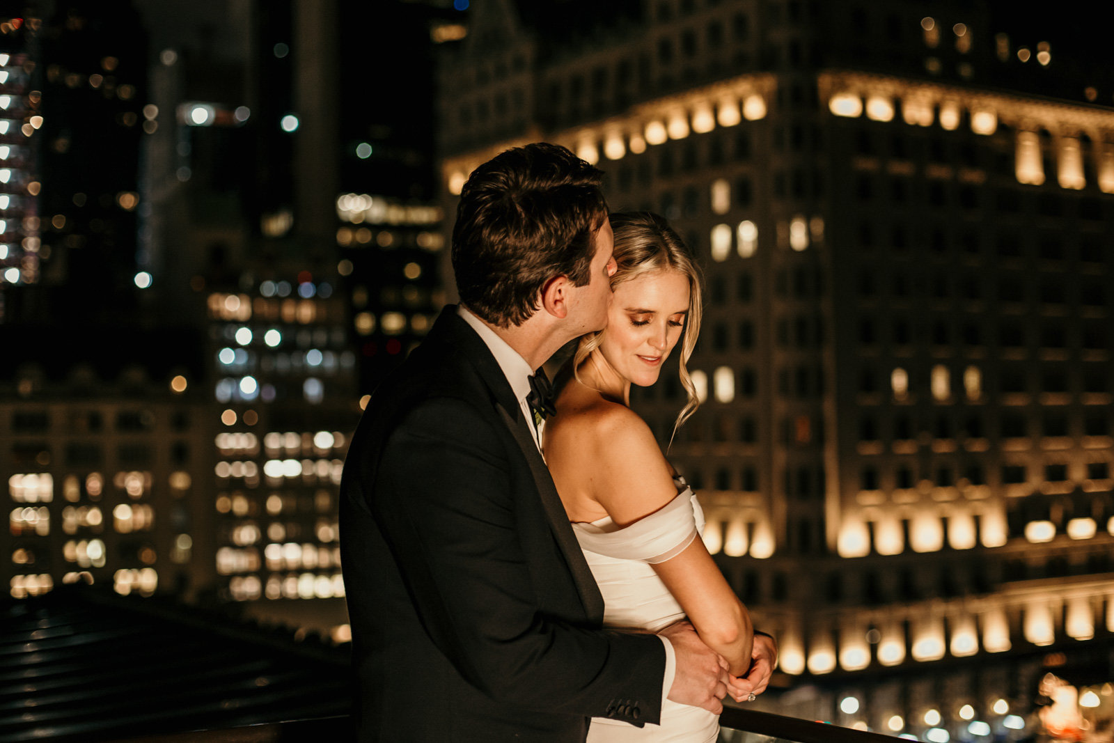 Bride and groom embrace on a rooftop in New York City.