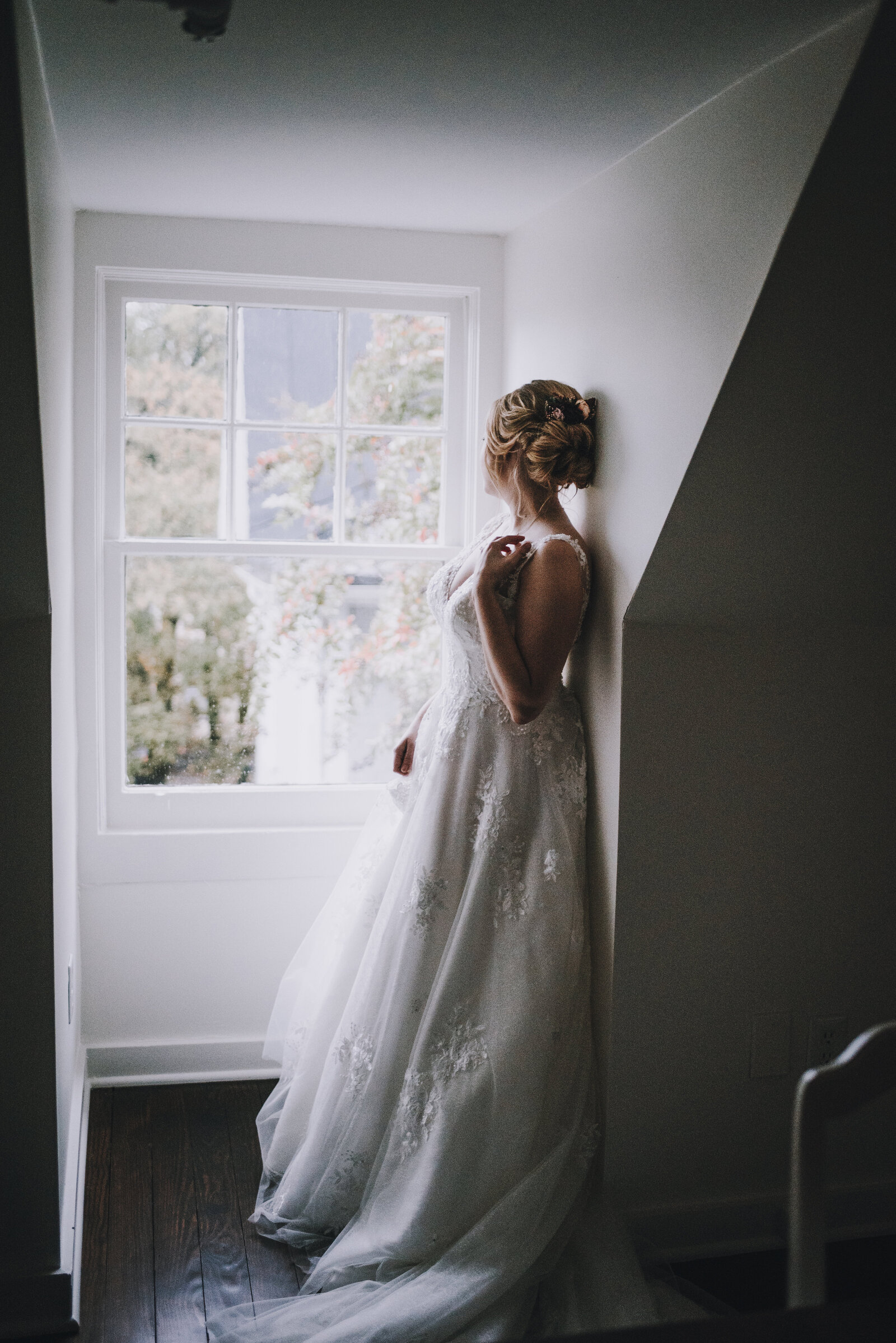 moody bridal session looking out window at wedding in Greensboro NC